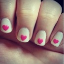 Nude nails with pink hearts.