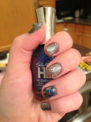Shiny grey nails with blue cheetah print and sparkles