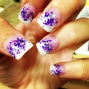 Acrylic nails with purple glitter.