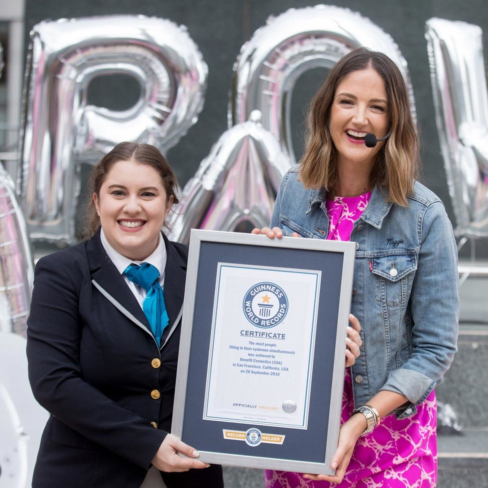 [Photo: Guinness World Records adjudicator Claire Stephens presenting certificate to Benefit Cosmetics Chief Beauty Ambassador Maggie Ford Danielson]