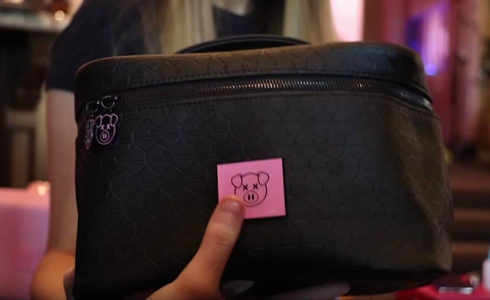 Shane Dawson Travel Bag embossed with little pig heads on spikes.