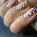 Nude nails with purple-gold polka dots