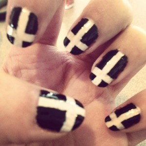 I painted my nails white, then once they dried I cut scotch tape into small strips and put them on my nails in the form of a cross, painted black over everything and peeled the tape off once fairly dry.