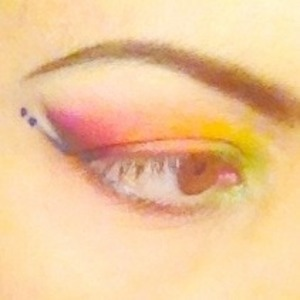 Inspiration: Bird of Paradise. Seven shadow colors (from inner to outer corner: lime green, taxi yellow, bold orange, warm red, Barney purple, light sparkly pink - under lashes- and gold-flecked ivory - on brow bone. Three liner colors (white - to line inner rim and as a highlight between the two other liner wings-, top wing lined from corner of eye outwards with a sparkly emerald green pencil and lower wing lined from corner of eye outwards with electric blue liquid. Two electric blue dots follow the tip of the lower wing. Lashes are bare.