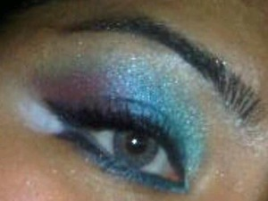 Use teal, blue, and purple ...work in sections on both top and bottom lid ..create two taiils with black liner before hand and in between place white shadow!!..highlight brown bone and inner corner !!!... mascara and white liner along the water line and presto!