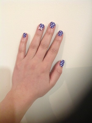 Purple nails with white polka dots Pink rhinestone bow on ring finger