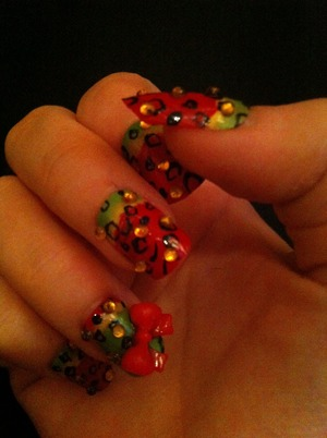 Simple cheetah design on a colourful background with rhinestones and 3D nail art glued on.
