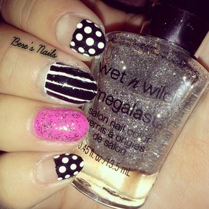 A simple black and white base with alternating stripes and polka-dots. Accented a nail with pink and glitter.