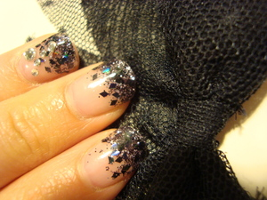 Simply a mix of small circular glitter pieces along with black diamond glitter pieces. Small gemstones are added to certain fingers. These are gel nails!