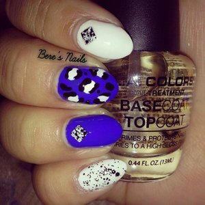 Blue and white as a base accented with a square black and white splattered stud. Monochrome black and white leopard print on the middle finger and a chunky black and white glitter on the pinky.