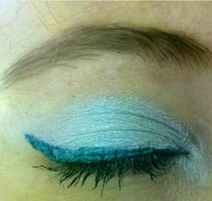 This picture doesn't capture the beauty of the eye shadow but it has flecks of blue and green sparkle. The blue is so pigmented. Sorry my lashes are crazy...I forgot to throw away my bad mascara and I picked it up and used it..I was running late so I didn't have time to fix it. The color is Frozen in Time. I also included an arm swatch with no base, white base, and black base from the companies site.