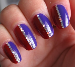 Purple and red nails, with a holographic glitter stripe.