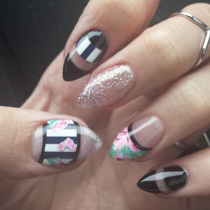 Acrylic stiletto nails with floral and striped patterns, glitter, negative space