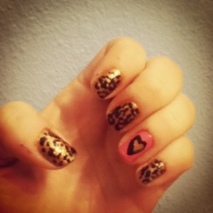 I started by painting my ring fingers pink and the rest of my nails gold. Then I added random large bronze dots to the gold nails using a dotting tool. I created a gold heart on my ring finger by making a v with a large brush and rounding out the edges. I created the black outline with a smaller brush. I finished off the leopard print with a small dotting tool and creating 4-5 small black dots around each larger bronze dot. To finish off, I put a top coat over all the nails.
