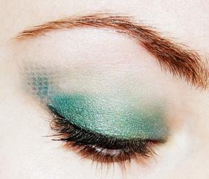 Green eye shadow used through lace.
