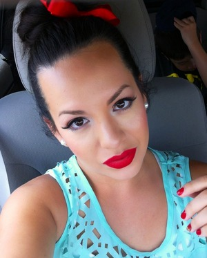 High bun with matching bow.  Bold red lip. Mint blouse.