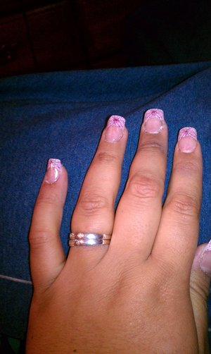 Acrylic nails with a pink french tip design.