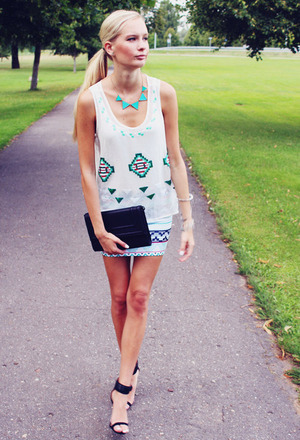 White sleeveless shirt, featuring round neckline, sleeveless, colorful sequined ethnic pattern embellished on body, loose fit. This sleeveless shirt goes with leisured shorts and flats when going out for a night snack.