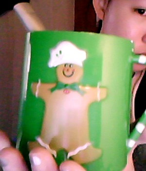me holding a gingerbread cup with a makeup brush in it, forgot to clean the brush :3